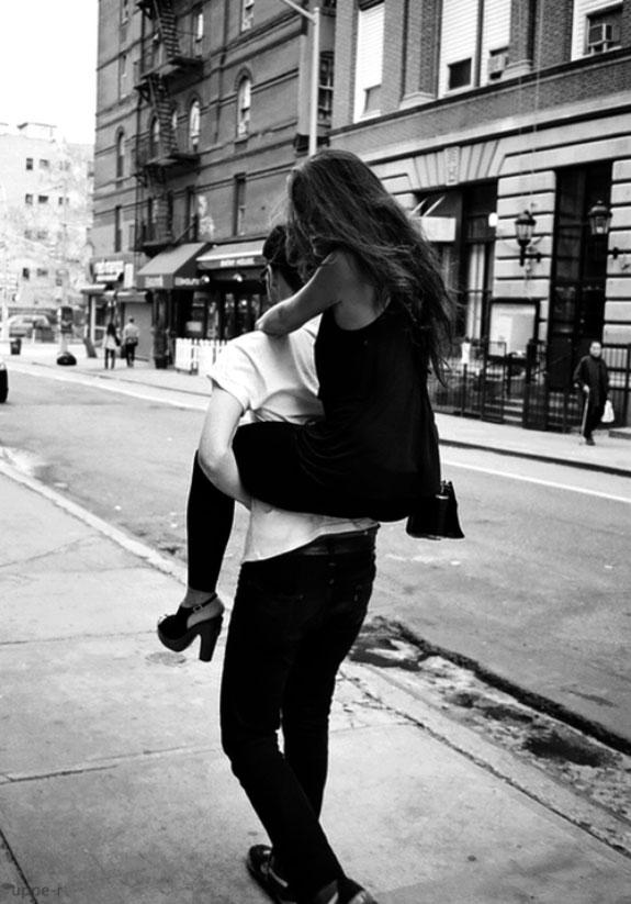 Black and white photo, guy carries a girl in a black dress