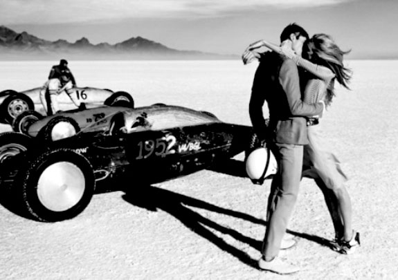 Black and white photo two people kissing in the dessert next to the racer car