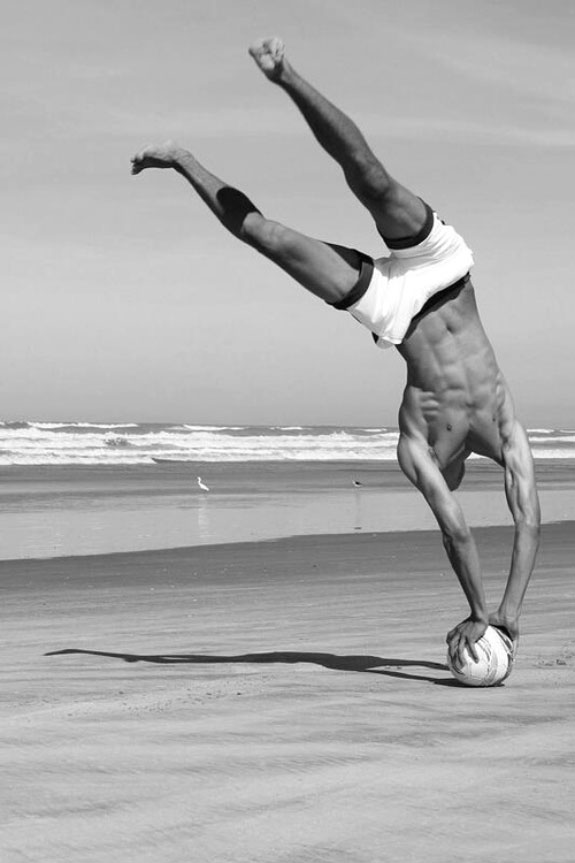 Black and white photo, guy on beach standing in a ball with his hands