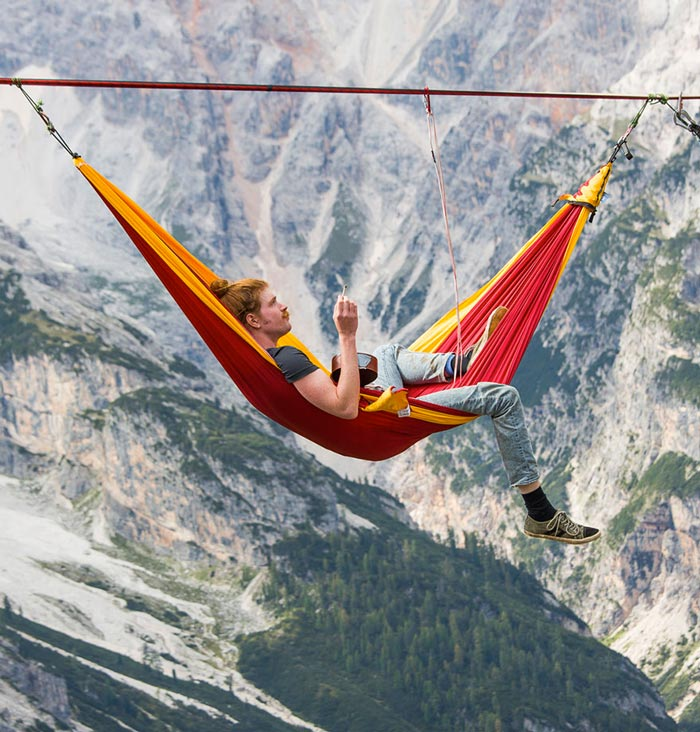 Man in a hammock on a slack line tight rope