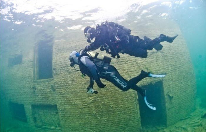Scuba divers at Rummu underwater prison