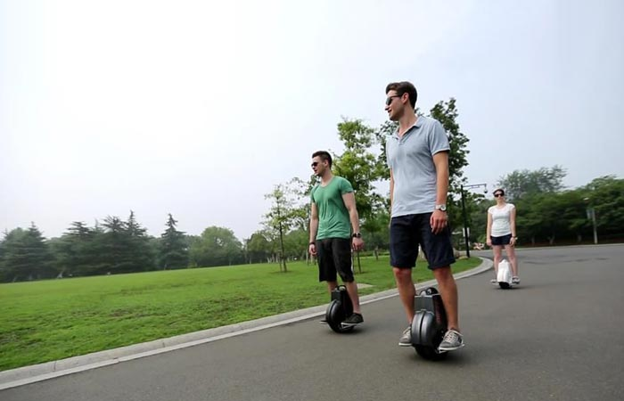 People using self balancing scooters on the street