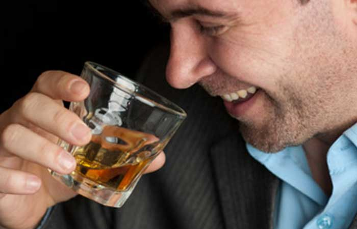 A man smiling while drinking whiskey