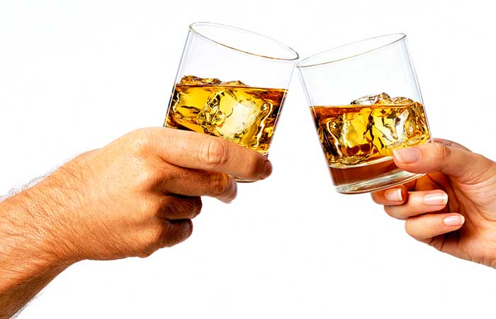 A man and a woman's hand with glasses of whiskey