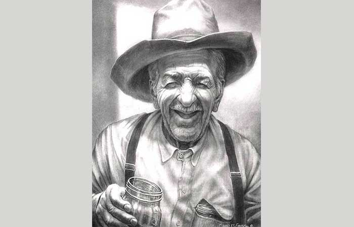 Old cowboy smiling with a glass of whiskey