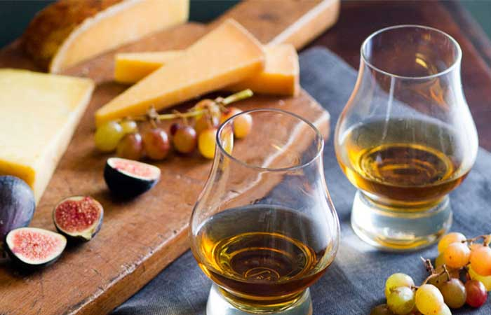Whiskey, cheese, grapes and plums