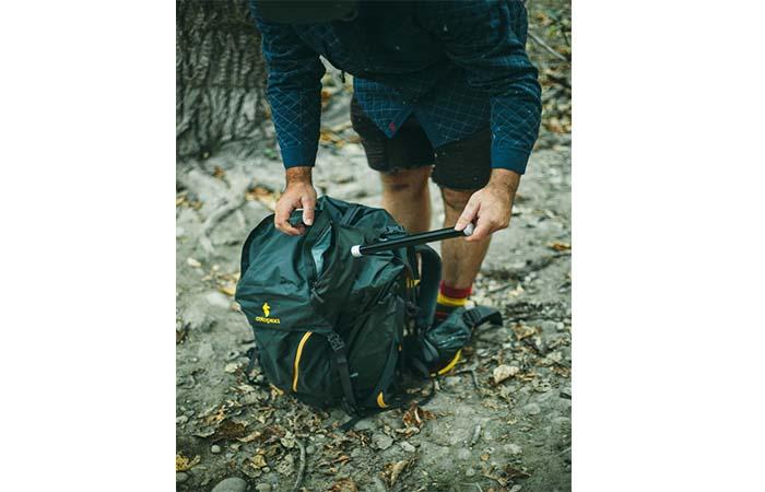A guy putting a Tenkara fishing rob in a backpack