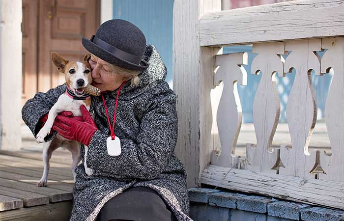 Older lady sitting on a porch with a dog wearing GPS location device