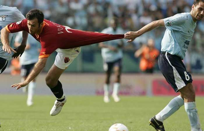 A soccer player pulling another soccer player's shirt