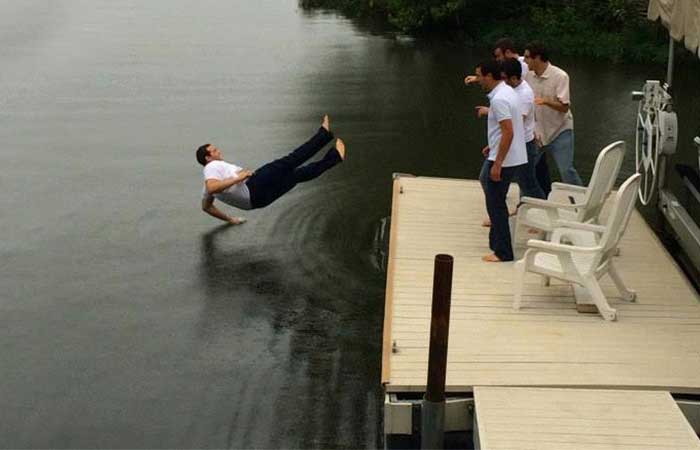 A man falling into water after being pushed by three friends