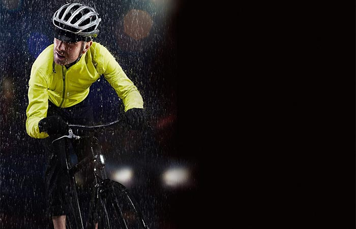 A guy wearing bright yellow jacket and riding a bike while raining