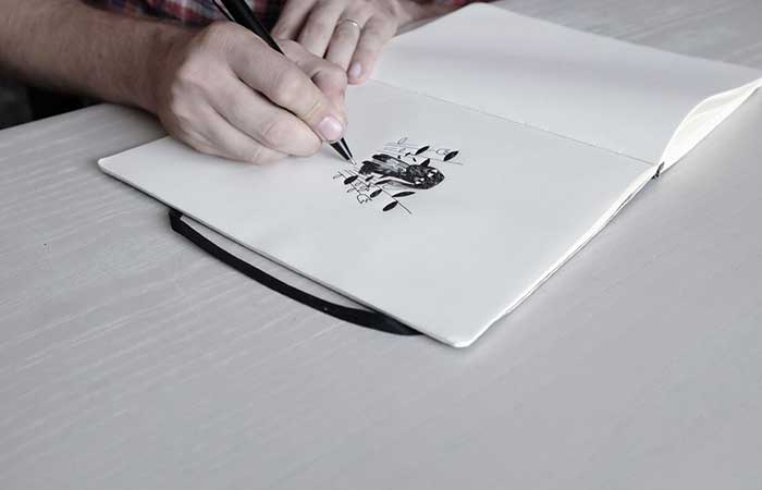 a man drawing in a notebook