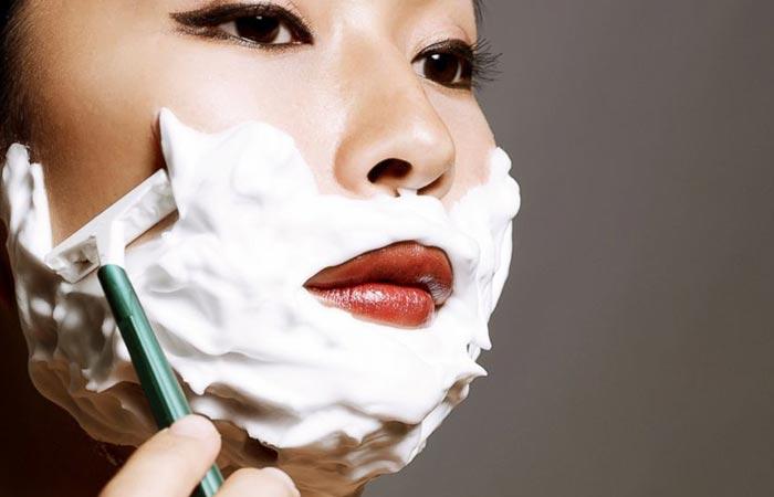 A woman shaving beard