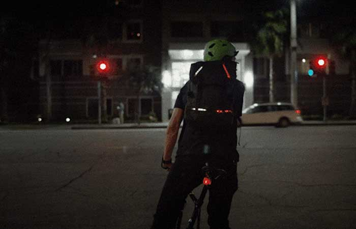 LED Illuminated and App Controled Active Apparel by Lumenus on a biker's backpack
