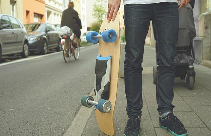 A guy holding Mellow Drive Electric Skateboard On The Street