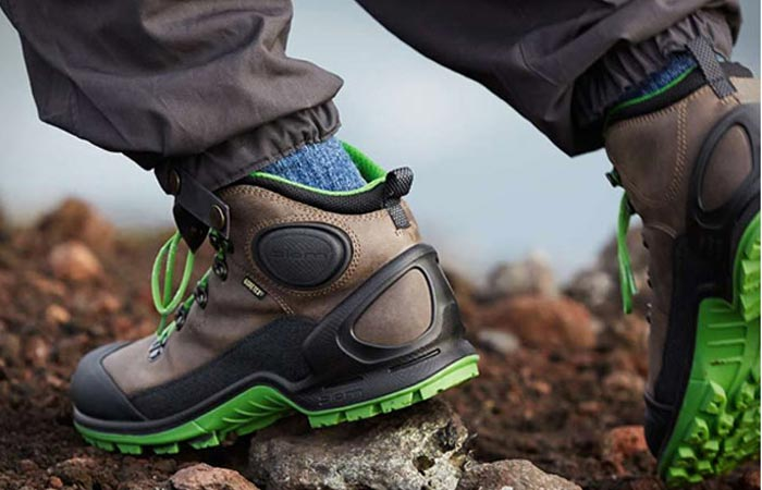 The Biom Terrain Hiking Boots green/gray, worn, on a rocky terrain.