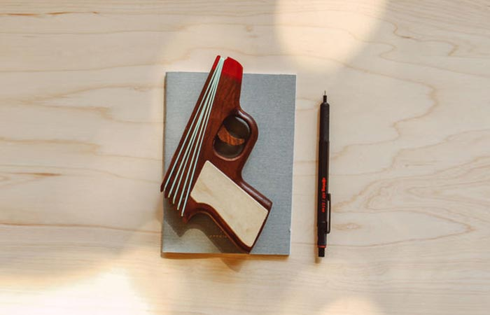 PPK Rubber Band Gun on a notebook next to a pen