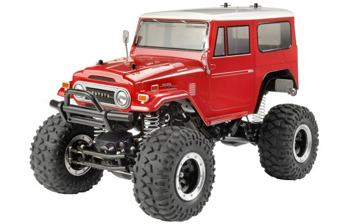 Tamiya RC Toyota Land Cruiser, red, tilted, on a white background.