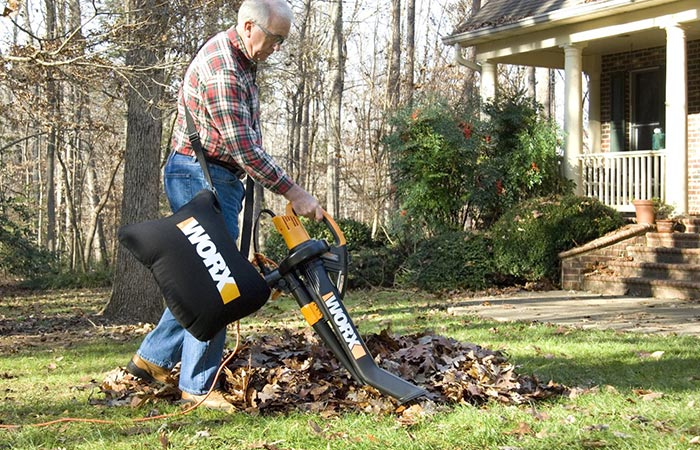 Older man cleaning leaves with WORX WG509 Electric TriVac BlowerMulcherVacuum
