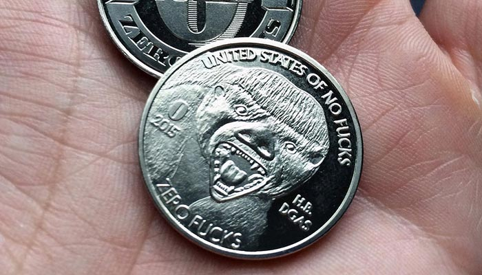 Honey Badger coins on someone's palm.