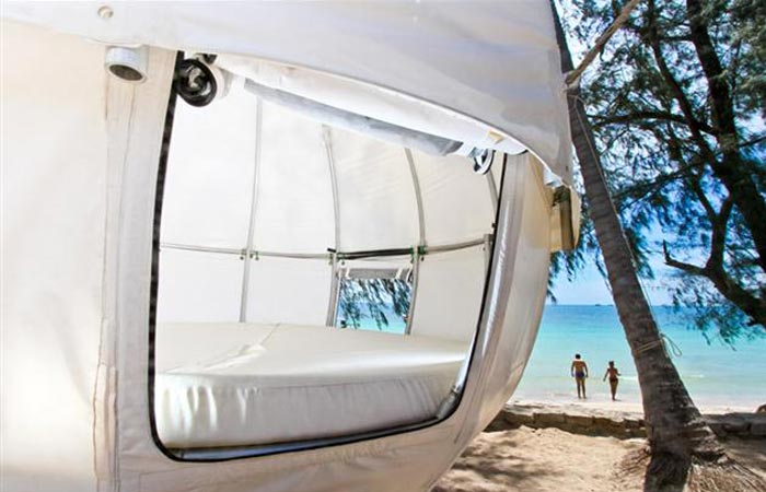 Cocoon Tent Treehouse hanging on the beach, a peak inside the tent.