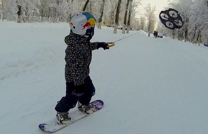 A little boy on a snowboard with a helmet being pulled across the snow by a drone.