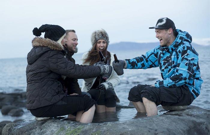 Four people sitting outside wearing Hanskie Beer Glove