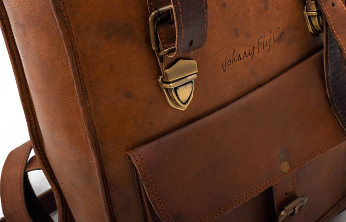 Leather Rolltop Backpack by Johnny Fly Co. zoomed in on the solid brass fittings and the front pocket.