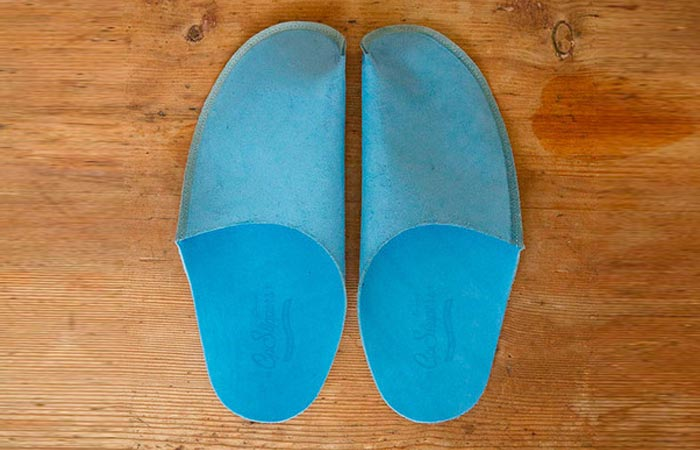 Luxurious Leather Slippers, blue, on a wooden surface.