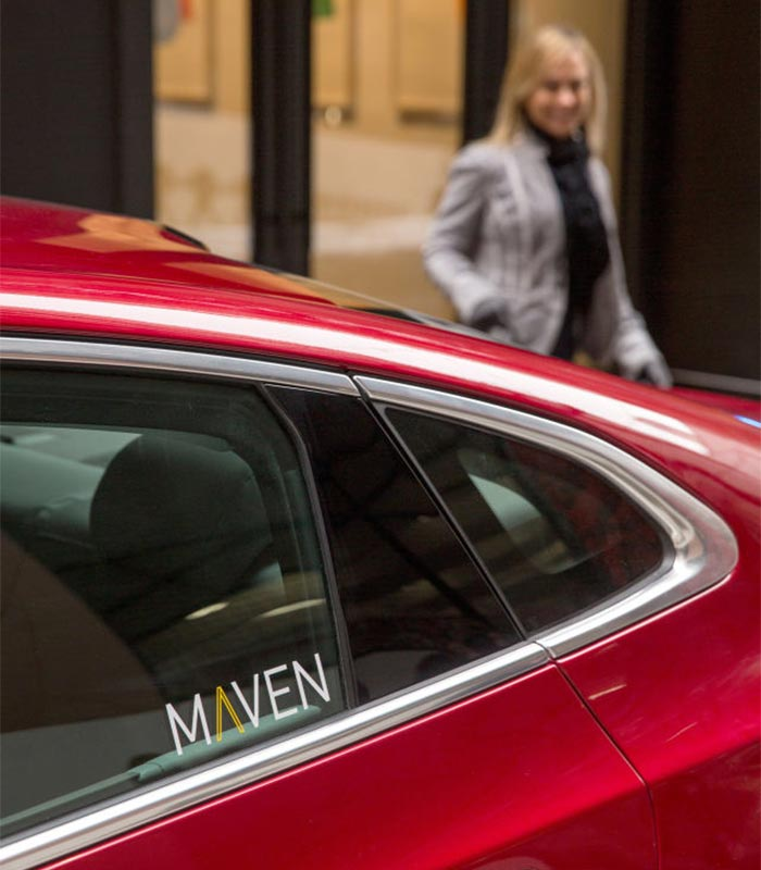 Red car with the maven sign captured from the side.