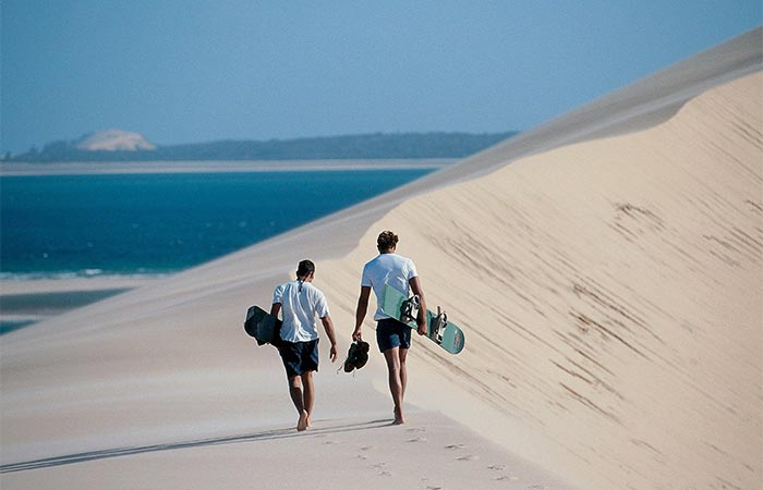 Two Guys Walking On A Sand Beach In Mozambique