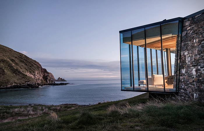 Seascape Retreat on a South Pacific Cove, a view at the glass terrace and the bay from the outside, at sundown.