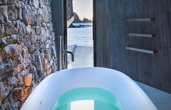Seascape Retreat on a South Pacific Cove indoor bathtub, filled with wate, with a view on the bay though the open door.