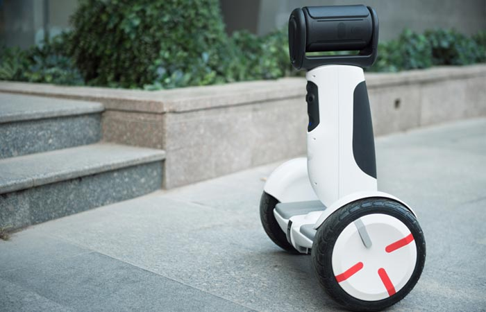 Segway Advanced Personal Robot balancing and navigating in the street in front of some stairs.