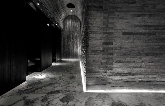 TUVE Boutique Hotel hallway with marble floor and black and grey textured walls.
