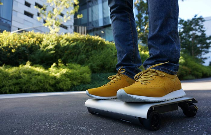 A person in yellow shoes riding the WalkCar.