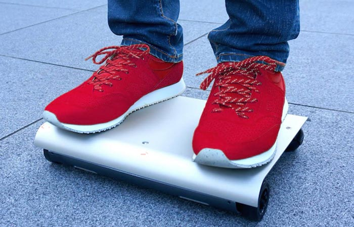 A person in red shoes riding a WalkCar.