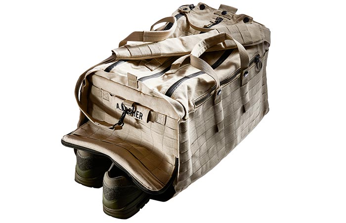 Able Archer Duffel, sand, side tilted view with a pair of shoes sticking out from one side.