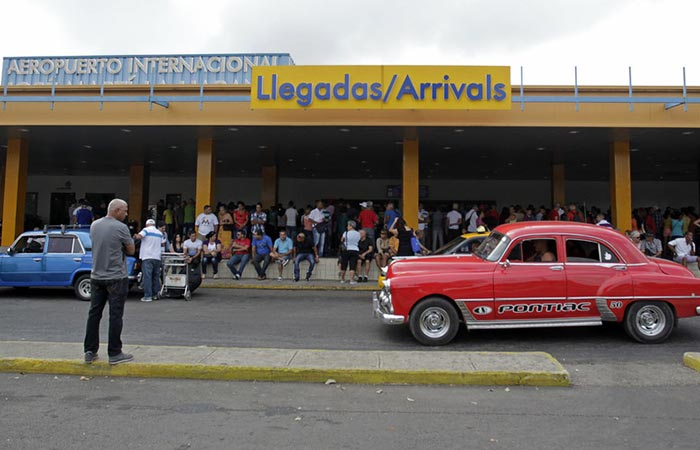 The street and people in front of the airport in Cuba.