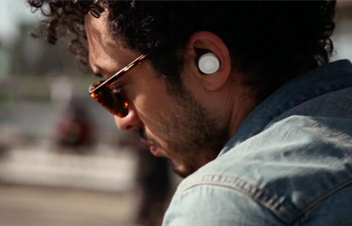 A man in the street with white Doppler Labs Here Active Listening Earbuds.