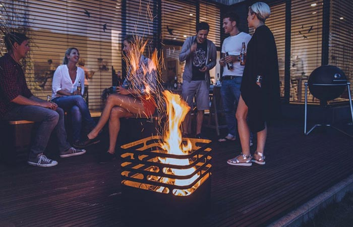 Höfats CUBE Fire Pit with fire lit inside, on a terrace, and people socializing in the background.