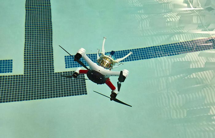Loon Copter, tilted, flying just above the pool full of water.