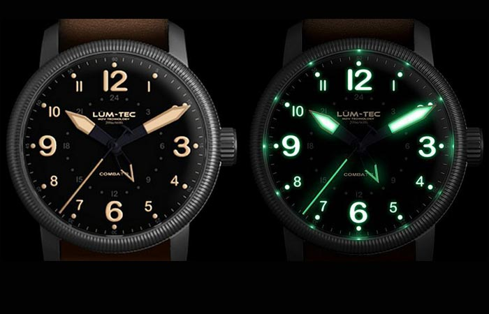Lum Tec Combat B33 GMT watch with white display and with old radium tone luminescence display, on a black background.