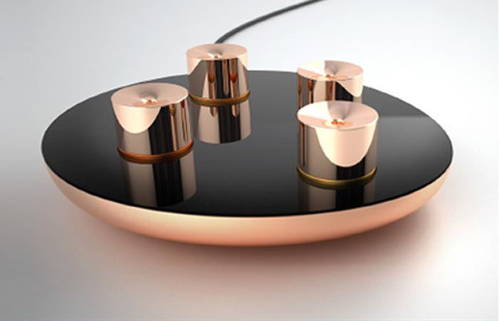 Lumiere Automated Essential Oil Diffuser with four capsules on a white surface with a shadow.