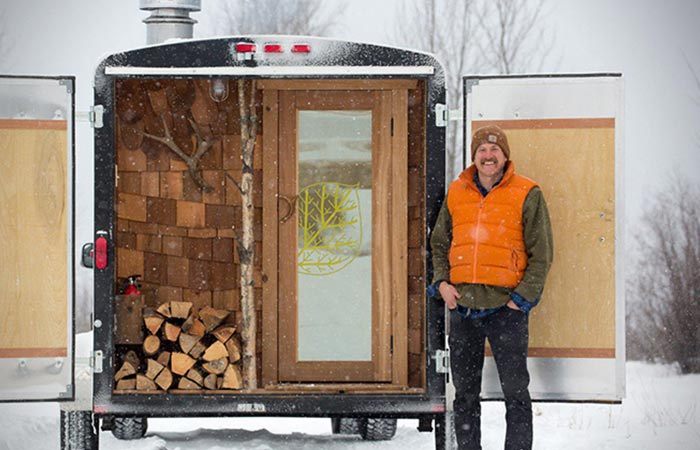 A man standing by the sauna on wheels.