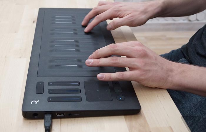 Roli Seaboard Rise laid on a wooden table, played with two hands.