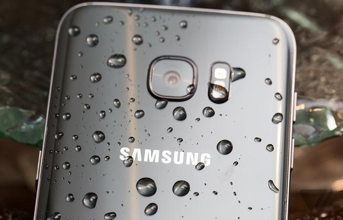 A phone captured from behind with water drops on it.