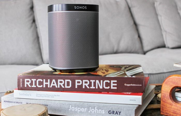Sonos speaker on a pile of books with a sofa in the background.