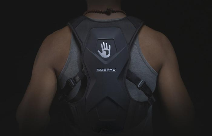SubPac M2on the back of a man in a grey sleeveless shirt, with a black background.
