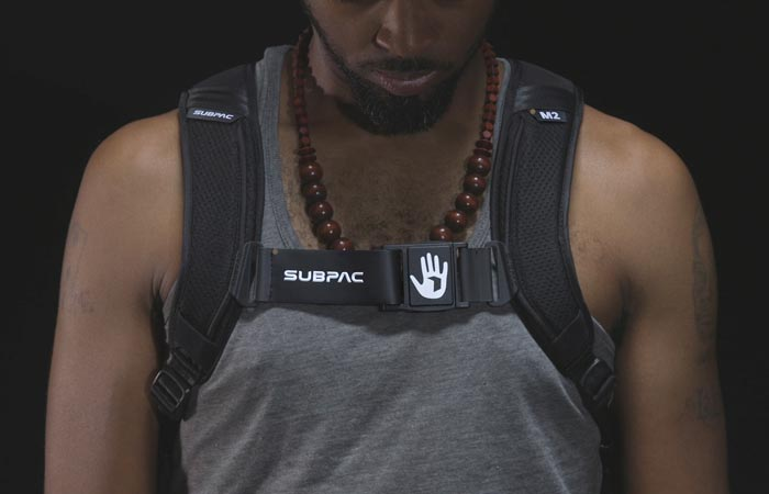 SubPac M2 worn by a man in a grey shirt, front view, with a black background.